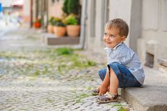 Little boy sits on the doorstep on a city street Stock Images