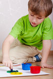 Little boy sits on floor and plays with paints Royalty Free Stock Images