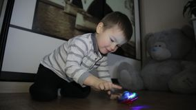 A little boy sits on the floor and plays with toys stock video footage