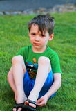 Little boy sits in the grass. A somber little 5 yr old boy in green shirt, blue shorts  and disheveled dark hair sitting in the grass. Shallow depth of field Stock Photography