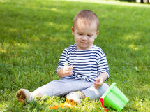 Little boy sits on a grass Royalty Free Stock Image