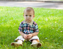 Little boy sits on a grass Stock Photo