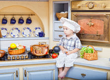 Little boy sits on a kitchen table Stock Images