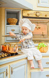 Little boy sits on a kitchen table Royalty Free Stock Photos