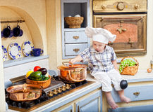 Little boy sits on a kitchen table Stock Photo
