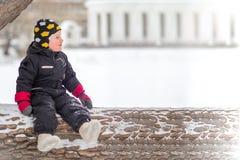A little boy sits on a large fallen tree in winter