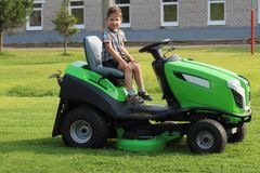 Little boy sits on lawn on green grass Stock Photo