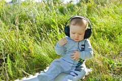 A little boy sits on a meadow with headphones Stock Photos