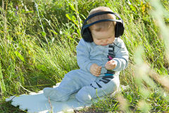 A little boy sits on a meadow with headphones Stock Photography