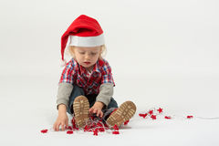 A little boy sits in modern clothes and hats Santa Claus Stock Photos
