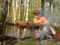 Little boy sits near campfire royalty free stock photos