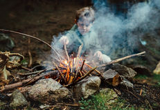 Little boy sits near campfire Royalty Free Stock Photo