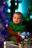 Little boy sits near Christmas tree and gift boxes. royalty free stock image