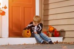 Little Boy Sits Near Halloween Pumpkin Royalty Free Stock Photo