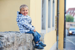 Little boy sits near the old house Royalty Free Stock Photos