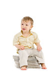 The little boy sits on a pile of books Royalty Free Stock Images