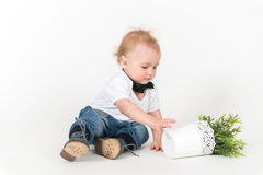 Little boy sits with the plant Royalty Free Stock Image