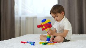 A little boy sits in a room on a bed and plays with meccano. stock video