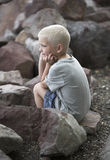 Little boy sits on rough rocks Royalty Free Stock Photography