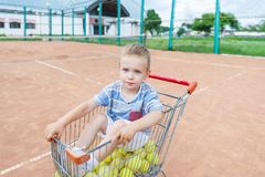 Little boy sits in a shopping trolley with tennis balls on clay court. royalty free stock photo