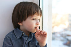 Little boy sits on sill and looks out of window in winter Royalty Free Stock Photography