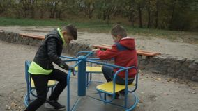 Two little boys spinning at the carousel at playground stock video footage
