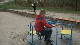 Little boy spinning on a swing at playground stock video