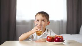 A little boy sits at a table and drinks fruit juice. Happy child laughs. Concept of healthy food for children and stock video