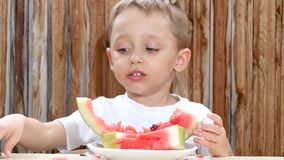 A little boy sits at the table and eats a juicy red watermelon. stock video footage