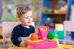 Little boy sits at table and plays with toy scales in playroom royalty free stock images
