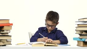 Little boy sits at a table and reads the book slowly. White background stock video
