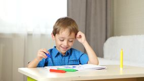 A little boy sits at a table in a room and draws, imagining a family. The child paint. emotions: happiness, joy stock video footage