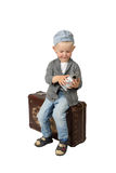 Little boy sits on vintage suitcase with alarm clock in hands Royalty Free Stock Image