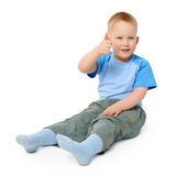 Little boy sits on white showing a gesture. A little boy sits on a white background showing a gesture thumb up Stock Photos