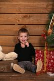 Little boy sits on a wooden floor near a Christmas tree Stock Photos