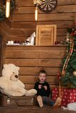Little boy sits on a wooden floor near a Christmas tree Stock Photography