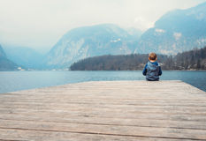 Little boy sits on the wooden pier near the blue mountain lake Royalty Free Stock Photography