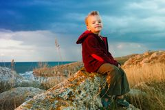 The little boy sitting against the sea Royalty Free Stock Photography