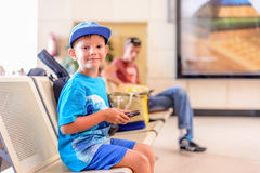 Little boy sitting in an airport departure hall Stock Photo