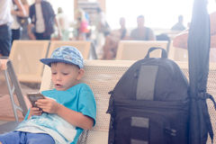Little boy sitting in an airport departure hall Stock Images