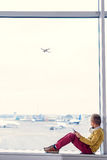 Little boy sitting at airport. Dream of flying. Little boy sitting on windowsill at airport hall and looking at plane taking off Royalty Free Stock Images