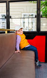 Little boy sitting alone in a bus. Cute little boy in a peak cap and bright orange jacket sitting alone in a bus or tram in an urban environment Royalty Free Stock Photography