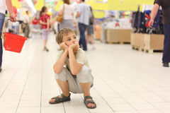 Little boy sitting alone on hunkers in big store Stock Photo