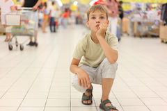 Little boy sitting alone on hunkers in big store Stock Image