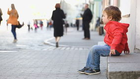 Little boy sitting alone in the street, people Stock Photography