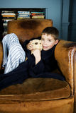 Little boy sitting in armchair with teddy bear Royalty Free Stock Photo