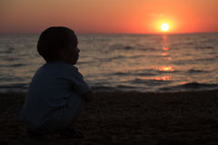 Little boy sitting back and watching the sunset Stock Image