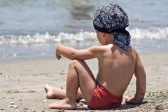 Little boy sitting on a beach Stock Photo