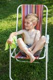 Little boy sitting in a beach chair. In the garden royalty free stock images
