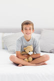 Little boy sitting on bed holding his teddy bear Royalty Free Stock Images